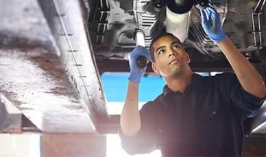 Mechanic Working under a Car in a Shop